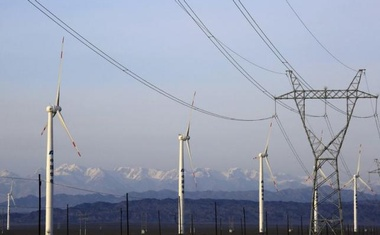 An electricity pylon is seen next to wind turbines at a wind power plant in Hami, Xinjiang Uighur Autonomous Region, China, March 21, 2015. REUTERS