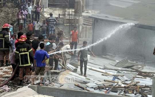 Fire-fighters taming the fire at a furniture shop in Dhaka's Panthapath on Sunday. Photo: tanvir ahammed