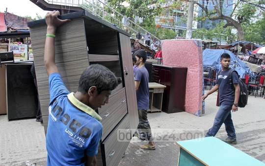 Furniture shop owners move out their merchandise after a fire at a shop in Dhaka's Panthapath on Sunday. Photo: tanvir ahammed