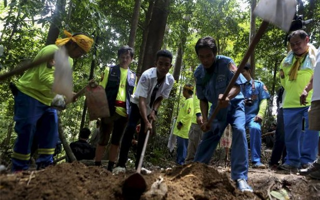 Rescue workers inspect a mass grave at an abandoned camp in a jungle in Thailand's southern Songkhla province May 5, 2015. REUTERS