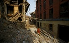 A woman walks along a street near collapsed houses, a month after the April 25 earthquake in Bhaktapur, Nepal May 25, 2015. Reuters