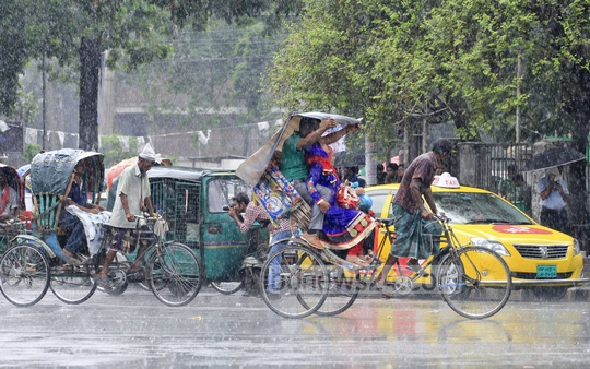 A burst of sudden rain brings respite from the scorching heat in Dhaka. People take cover under polythene sheet on the Dhaka University campus on Monday. Photo: asif mahmud ove