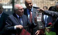 FIFA chief Sepp Blatter (L) receives a gift from Palestinian children during his visit to Dura al-Qar' village in the West Bank city of Ramallah, REUTERS