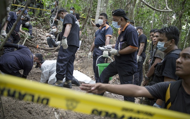 Policemen monitor as forensic experts dig out human remains near the abandoned human trafficking camp in the jungle close the Thailand border at Bukit Wang Burma in northern Malaysia May 26, 2015. Reuters