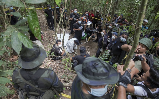 Policemen and reporters monitor as forensic experts dig out human remains near the abandoned human trafficking camp in the jungle close the Thailand border at Bukit Wang Burma in northern Malaysia May 26, 2015. Reuters