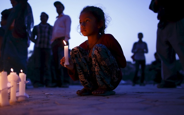 A girl holding a candle takes part in a candlelight vigil, a month after the April 25 earthquake, in Kathmandu, Nepal May 25, 2015. Reuters