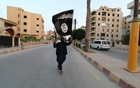 A member loyal to the Islamic State in Iraq and the Levant (ISIL) waves an ISIL flag in Raqqa June 29, 2014. Reuters