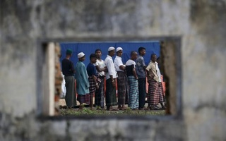 Rohingya migrants who arrived in Indonesia by boat are seen through the window of an abandoned building as they wait in line for breakfast at a temporary shelter in Aceh Timur regency near Langsa in Indonesia's Aceh Province. Reuters