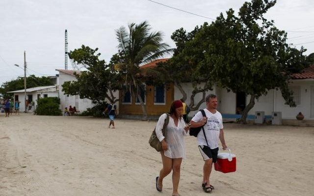 Tourists walk on the street at the Gran Roque island, in the archipelago of Los Roques May 29, 2015. Reuters