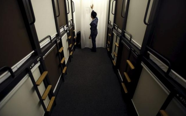 A hotel staff member touches a curtain in a corridor between one man capsule bed units called 'pods' inside a hotel at Grids at the Akihabara shopping district in Tokyo, Japan, May 19, 2015. Reuters