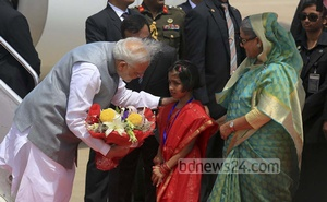 Narendra Modi carrying a bouquet presented by a child at the airport in Dhaka. The Indian prime minister was accompanied by his Bangladesh counterpart Sheikh Hasina. Photo: mustafiz mamun