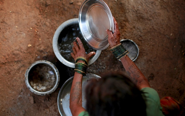 Sakhri, the second wife of Sakharam Bhagat washes utensils outside their house in Denganmal, Maharashtra, India. REUTERS