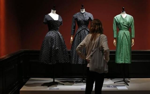 A visitor looks at vintage dresses by designers Christian Dior, Jacques Heim and Givenchy presented in the exhibition 'Les Annees 50, La mode en France' (The 50s. Fashion in France, 1947-1957) at the Palais Galliera fashion museum in Paris, July 10, 2014. Reuters