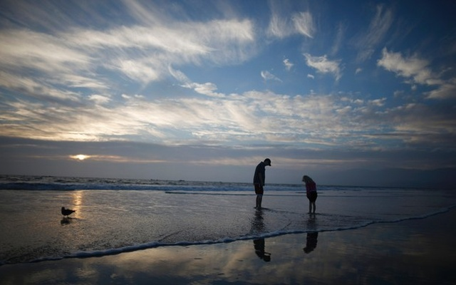 A man and a girl paddle in the Pacific Ocean at sunset in Santa Monica, California, Feb 5, 2015. Reuters