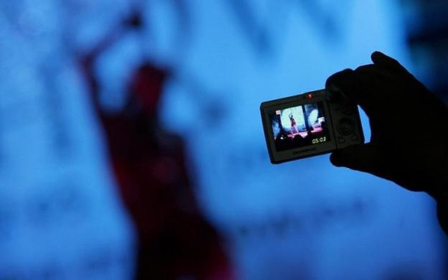 A visitor takes pictures of an adult film actress during the Eros Show in the Bulgarian capital Sofia April 2, 2008.