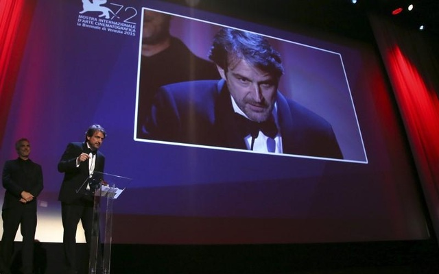 Director Lorenzo Vigas (R) makes a speech after he received the Golden Lion prize for his movie