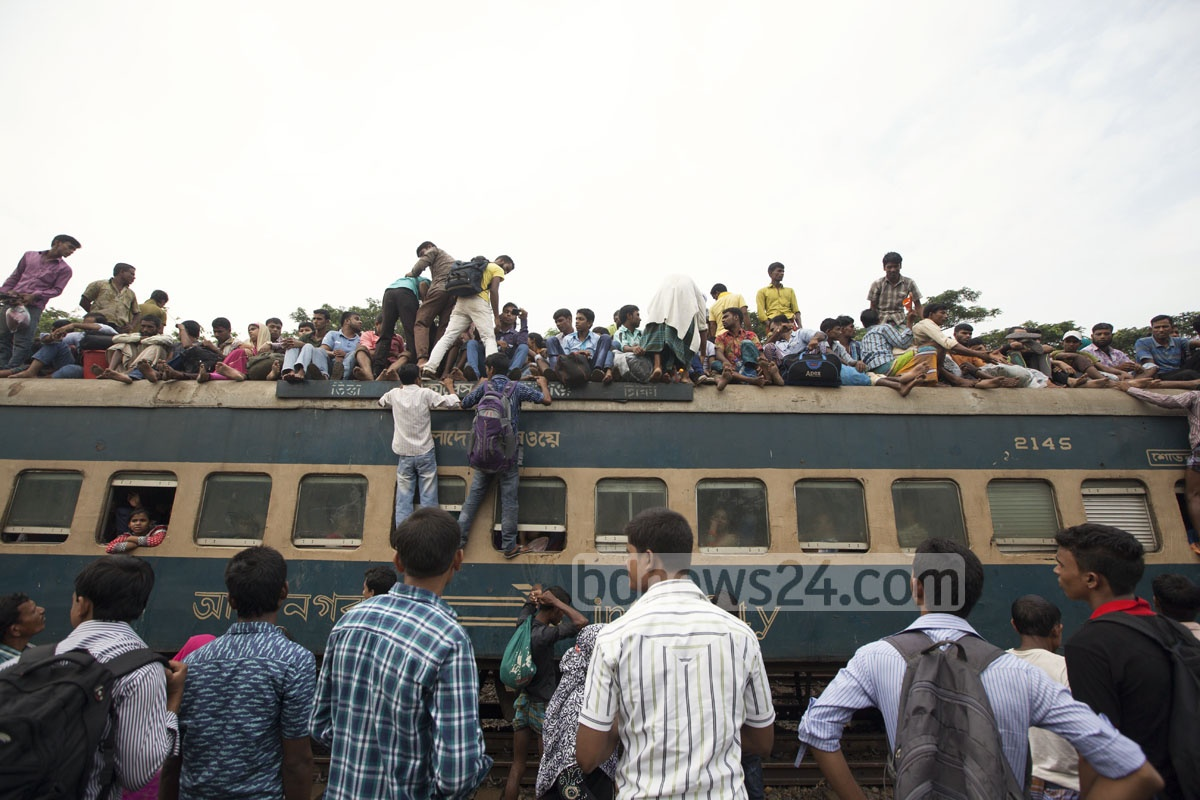 People, desperate to get home before the Eid-ul-Azha, climb on the roof of a train at the Airport Railway Station in Dhaka on Thursday.