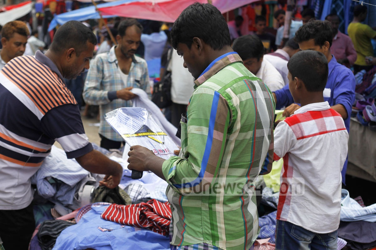 Low-income people browse through clothes at a shop on a footpath on Thursday at Dhaka's Motijheel ahead of Eid-ul-Azha. Photo: nayan kumar