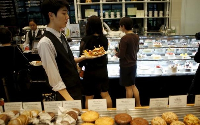 An employee serves sandwiches during lunchtime at a bakery in central Seoul, South Korea, Oct 13, 2015. Reuters