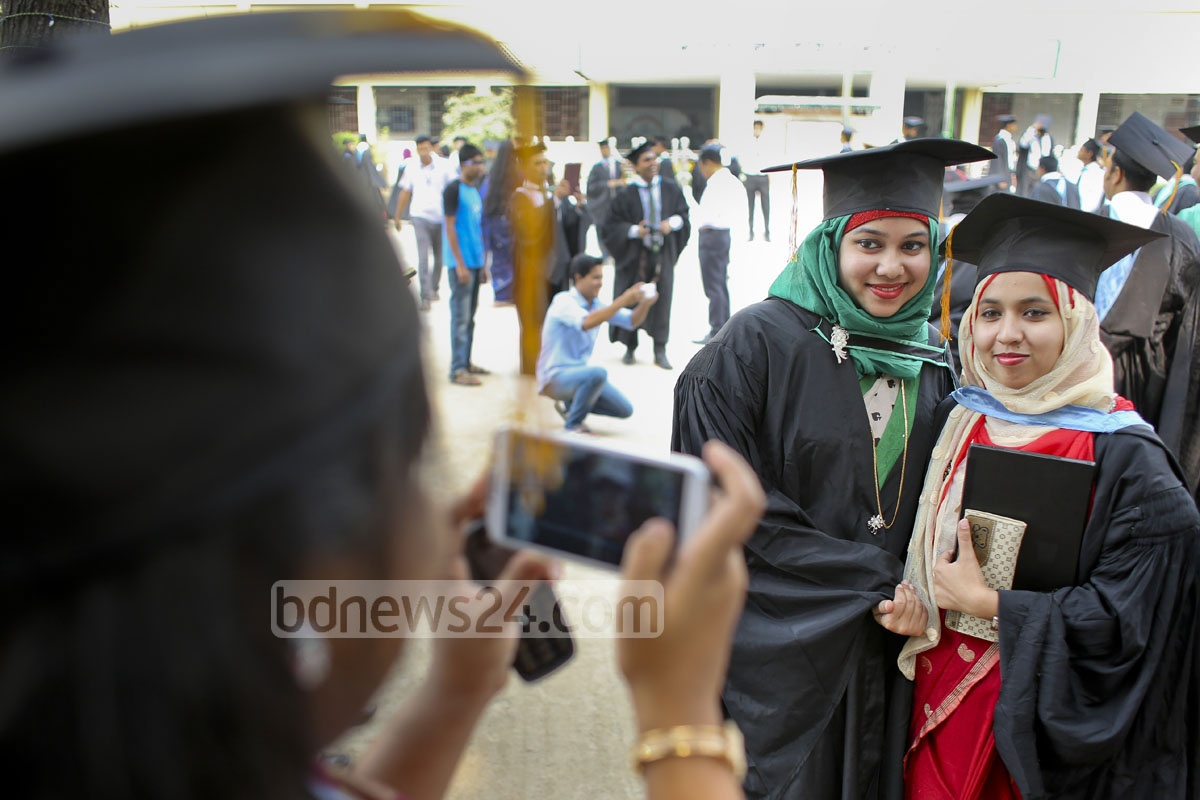A student takes a photo as others pose wearing convocation gowns and caps.