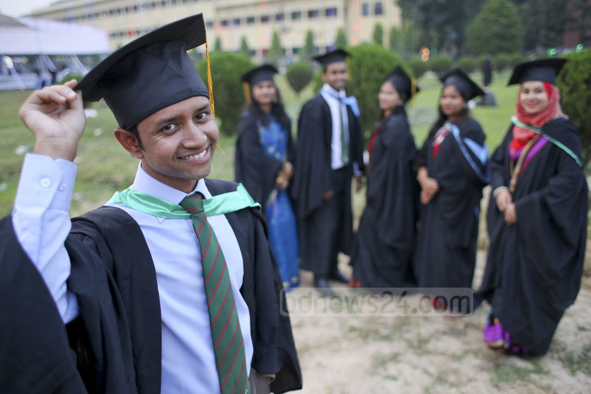 Students smile wearing gowns and caps at the convocation.
