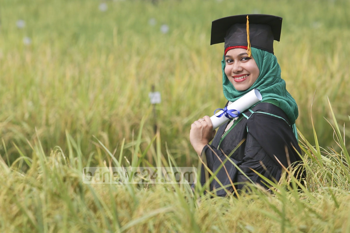 A student smiles wearing gown and cap at the convocation.