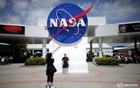 Tourists take pictures of a NASA sign at the Kennedy Space Center visitors complex in Cape Canaveral, Florida April 14, 2010. Reuters