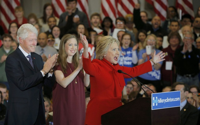 Former US President Bill Clinton (L) applauds his wife, Democratic US presidential candidate Hillary Clinton (R), as they appear with their daughter Chelsea (C) at Mrs. Clinton's caucus night rally in Des Moines, Iowa February 1, 2016. reuters