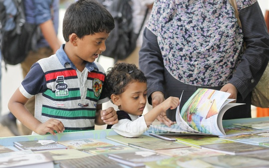 A child, helped by its mother, looks at a book with wonder at the book fair on Thursday. Photo: nayan kumar