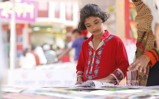 A kid engrossed in a book during Children's Hour at the book fair on Friday. Photo: nayan kumar
