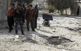 Men stand near a hole in the ground as they inspect the damage after airstrikes by pro-Syrian government forces in the rebel held al-Sakhour neighbourhood of Aleppo, Syria February 5, 2016. Reuters