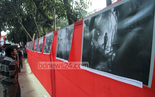 A visitor admires photos on the life of teagarden workers at a show in Dhaka University campus on Saturday.