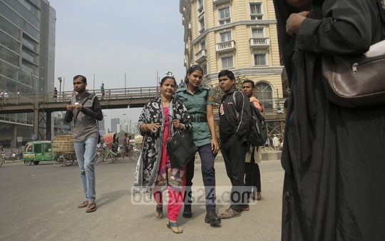 Police stop a woman for jaywalking at Bangla Motor on Sunday. Photo: tanvir ahammed