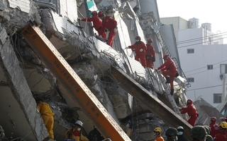 Rescue personnel work at the site where a 17-story apartment building collapsed from an earthquake in Tainan, southern Taiwan, February 7, 2016. Reuters