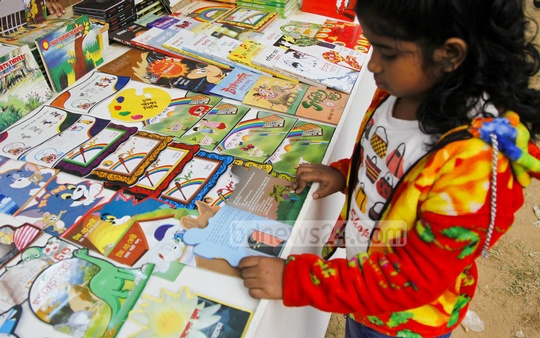 A child makes a selection of books at the Amar Ekushey Book Fair on Sunday. Photo: nayan kumar