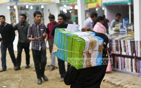 A man carries new books to a stall at the Amar Ekushey Book Fair on Sunday. New books are arriving at the daily. Photo: nayan kumar