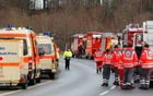 Cars of firefighters and ambulances are parked along a road near Bad Aibling in southwestern Germany, Feb 9, 2016. Reuters
