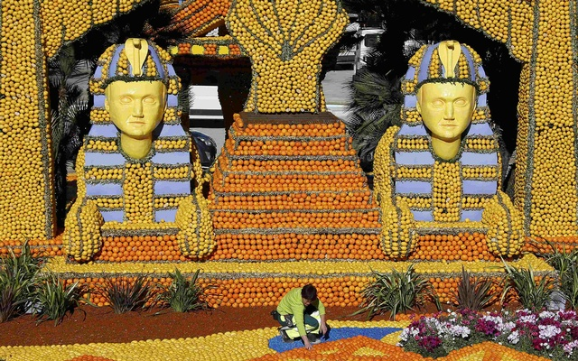 A worker puts the final touch to a replica of a giant pharaons made with lemons and oranges which shows a scene of the movie