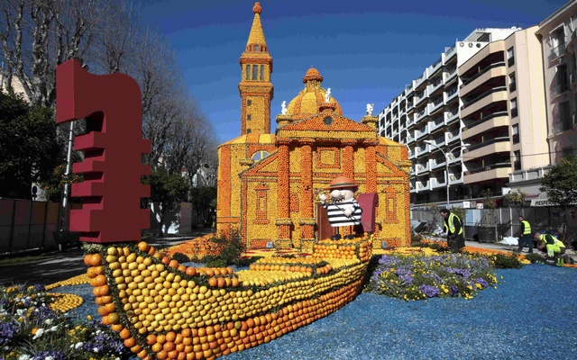 Workers put the final touch to a replica of a gondola and a Venetian palace made with lemons and oranges which shows a scene of the movie