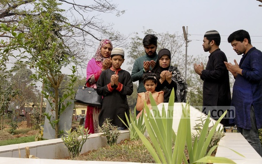 Family and relatives of journalist couple Sagar Sarowar and Meherun Runi offer prayers at their graves at Azimpur on Thursday, the fourth anniversary of their murder. Photo: tanvir ahammed