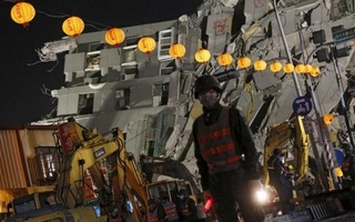Soldiers stand guard in front of 17-storey apartment building collapsed after an earthquake, on the first day of the Chinese Lunar New Year at Tainan, southern Taiwan, Feb 8, 2016. Reuters