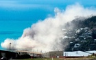 Dust and debris rise above houses after a cliff collapsed due to an earthquake on the Whitewash Head area, located above Scarborough Beach in the suburb of Sumner, Christchurch, New Zealand, Feb 14, 2016. Reuters