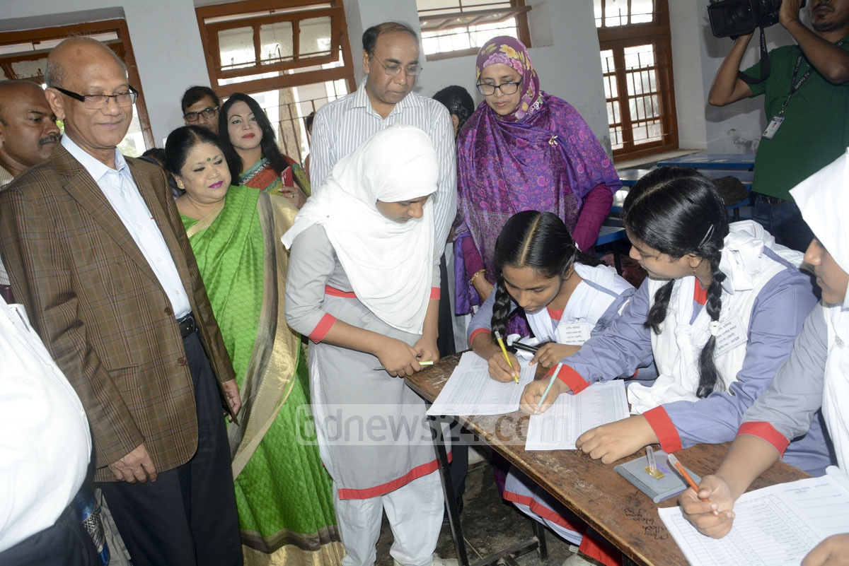 A student checks her name on the voter list while Education Minister Nurul Islam Nahid looks on during the election to 'student cabinet' at Dhaka's Motijheel Govt Girls School on Monday.