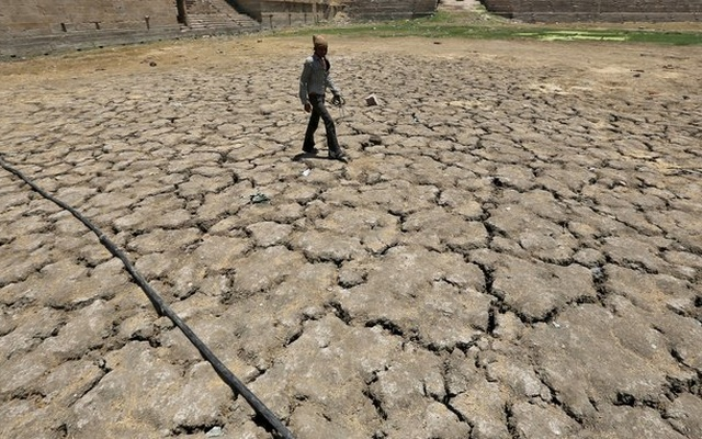 A man walks through a dried-up Sarkhej lake on a hot summer day in Ahmedabad, India, April 21, 2016. Picture taken April 21, 2016. REUTERS/Amit Dave