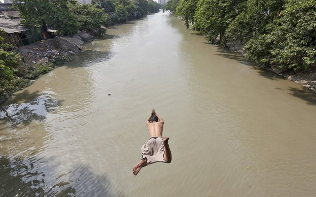 A man jumps into Tolly's Nullah to cool off on a hot day in Kolkata, India, April 25, 2016. reuters