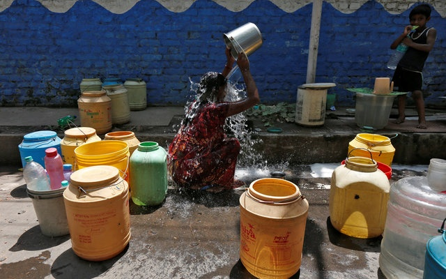 A woman bathes at a roadside municipal tap in a slum area on a hot summer day on the outskirts of Kolkata, India, April 22, 2016. reuters