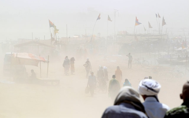 People walk through a dust storm on the banks of the Ganga river in Allahabad, India, April 12, 2016. reuters