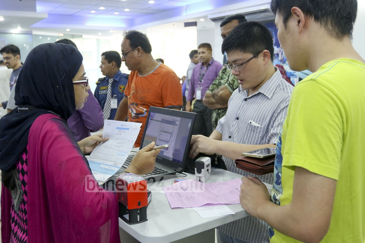 Foreigners get their mobile-phone SIM cards re-registered with biometric details at a Farmgate centre. Photo: abdul mannan