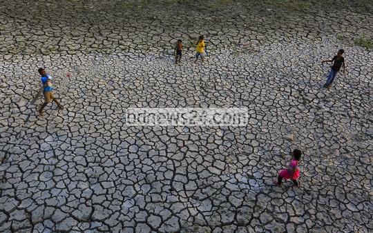 Children play cricket on a field at Beraid under Dhaka's Bhatara which has cracked due to drought.
