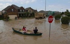 A woman holds a baby in a canoe as Texas Guardsmen arrive to assist after flooding in Brookshire, Texas, U.S. April 20, 2016. Reuters